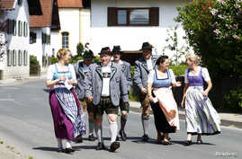 People in traditional clothes arrive to cast their vote for the European Parliament elections in Haunshofen near Starnberg, Germany, May 25, 2014.