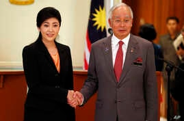 Thai Prime Minister Yingluck Shinawatra, left, and her Malaysian counterpart Najib Razak pose for photographers after their joint press conference at the latter's office in Putrajaya, Malaysia, February 28, 2013.
