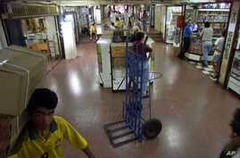 FILE - A man carries boxes at the Page shopping center in the border city of Ciudad del Este, Paraguay, in this Nov. 30, 2001, photo. Paraguayan police raided a wholesale electronic goods store in this shopping center, seizing documents, videotapes a