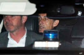 Former French President Nicolas Sarkozy, right, leaves the police station where he was held, in Nanterre, outside Paris, March 21, 2018. Sarkozy was questioned by police for a second day over allegations he took millions of euros in illegal campaign