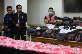 Members of the National Bureau of Investigation stand guard near bags containing nearly one metric ton of seized methamphetamine during a press conference in Manila, Dec. 27, 2016.