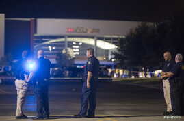 Officials stand by the scene outside the movie theatre where a man opened fire on film goers in Lafayette, Louisiana, July 23, 2015.