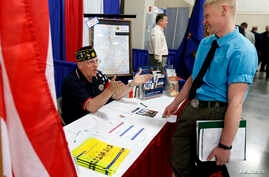 """A U.S. veteran gets information at the Veterans Administration booth at the """"Hire Our Heroes"""" Job fair in Sandy, Utah, March 25, 2014."""