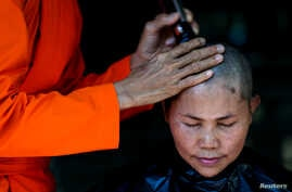A devotee has her hair cut by a female Buddhist monk during a mass female Buddhist novice monk ordination ceremony at the Songdhammakalyani monastery, Nakhon Pathom province, Thailand, Dec. 5, 2018.