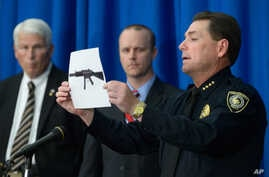 University of Central Florida police Chief Richard Beary, right, shows an example of the assault rifle, along with explosive devices, found in the dorm room of James Oliver Seevakumaran, Monday, Mar. 18, 2013, in Orlando, Fla.