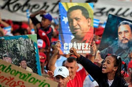 Posters during the annual May Day march in Revolution Square in Havana, Cuba show images of Fidel Castro and Venezuela's late President Hugo Chavez ,  May 1, 2013.