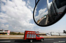 FILE - A truck is reflected in a rear-view mirror at Mexico-Puebla highway, on the outskirts of Mexico City, Mexico, March 8, 2018.