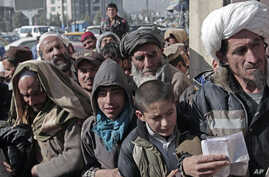 FILE - Afghan men and boys wait in line to receive their donated sacks of wheat distributed by the World Food Program in Kabul, Afghanistan, Dec. 15, 2013.
