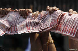 Anti-government protesters hold Thai baht banknotes to donate to protest leader Suthep Thaugsuban (unseen) as he leads a march through central Bangkok, March 28, 2014.