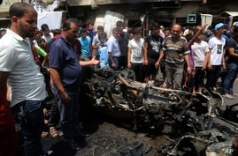 Citizens inspect the scene after a car bomb explosion at a crowded outdoor market in the Iraqi capital's eastern district of Sadr City, Iraq, May 11, 2016.