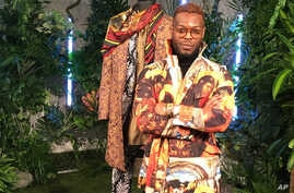 """Wale Oyejide, founder of the brand Ikire Jones, stands with his menswear design for a fashion collection inspired by the superhero film """"Black Panther,""""  Feb. 12, 2018, in New York."""
