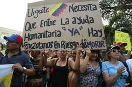 """Venezuelans living in Colombia protest the government of Venezuela's President Nicolas Maduro and its blocking of humanitarian aid in Cucuta, Colombia, Feb. 12, 2019. The sign reads, """"Urgent. The entry of humanitarian help is needed now. There are Ve"""
