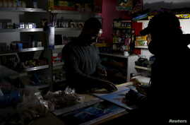 A shopkeeper counts change by the light of a battery-powered lamp during a load-shedding electricity blackout in Cape Town, South Africa, April 15, 2015.