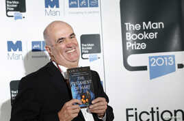 "Man Booker Prize 2013 shortlist nominee Colm Toibin poses with his book ""The Testament of Mary"" during a photocall at the Southbank Centre in London, October 13, 2013."