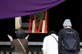 Religious offerings dedicated by Japanese Prime Minister Shinzo Abe are seen, center in the background, as people pray at the Yasukuni Shrine in Tokyo during an annual spring festival, April 21, 2015.