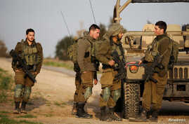 Israeli soldiers stand near a military jeep next to the border fence with the southern Gaza Strip near Kibbutz Nirim, Israel, Feb. 17, 2018.