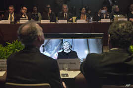 Participants at the Global Alliance for Clean Cookstoves summit view monitors showing former U.S. Secretary of State Hillary Rodham Clinton as she delivers keynote remarks in New York, Nov. 21, 2014.