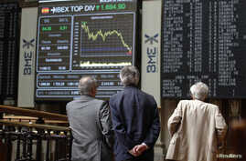 Traders look at electronic boards at the stock exchange in Madrid, June 11, 2012.