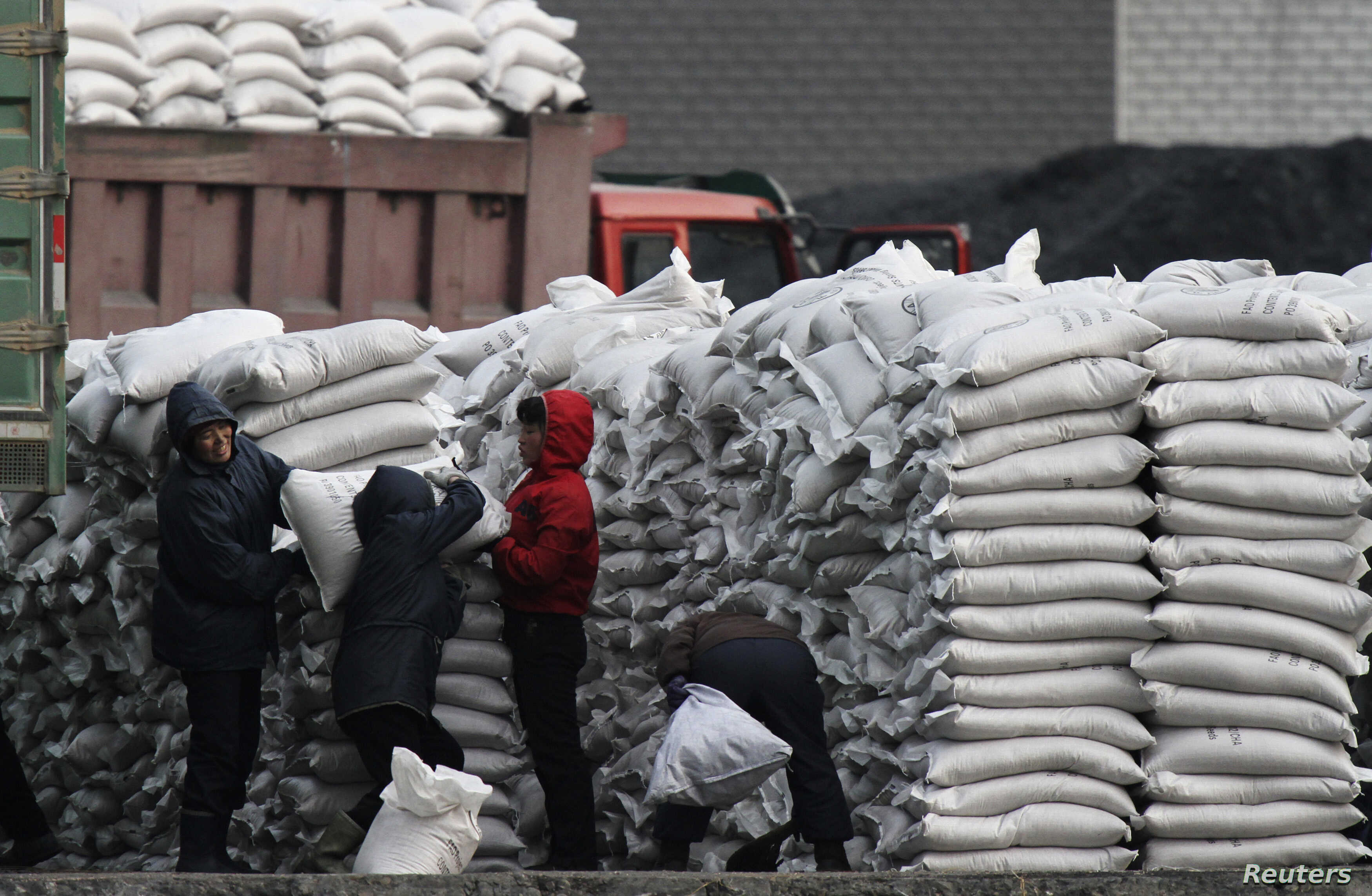 FILE - North Koreans distribute imported sacks of flour on the banks of Yalu River, near the North Korean town of Sinuiju, opposite the Chinese border city of Dandong, Jan. 27, 2014.