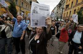 Activists hold leaflets reading 'In Support of Navalny' with a photo of opposition leader Alexei Navalny who was convicted of embezzlement and sentenced to five years in prison, in St. Petersburg, Russia, July 18, 2013.