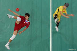 FILE - Thailand's Tidawan Daosakul (red) plays the ball against Vietnam's Nguyen Hai Thiao during their women's sepak takraw regu final at the 2010 Asian Games.
