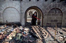 A nun looks at a heavily damaged Church of Multiplication after a fire broke out overnight near the Sea of Galilee in Tabgha, Israel, June 18, 2015.