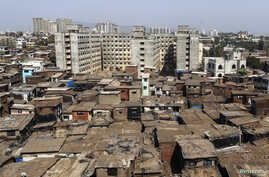 FILE - High-rise residential buildings are seen behind a cluster of houses at a slum in Mumbai, May 6, 2014.