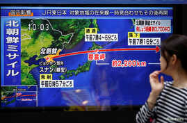 A passer-by looks at a TV screen reporting news about North Korea's missile launch in Tokyo, Japan, Sept. 15, 2017.