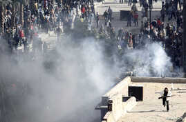 An armed man runs on a rooftop during clashes between police and protesters in Suez, Egypt, Jan. 28, 2011.
