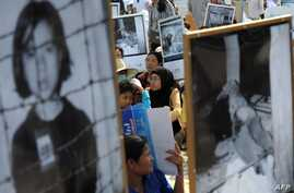 Cambodians hold portraits of Khmer Rouge victims during a protest in Phnom Penh in this June 9, 2013, file photo.