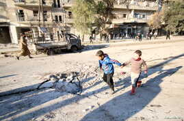 Boys run near a hole in the ground after airstrikes by pro-Syrian government forces in the rebel-held al-Sakhour neighborhood of Aleppo, Syria, Feb. 8, 2016.