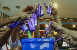 Members of Malaysian Muslim Wholesalers and Retailers Association (MAWAR), a non-governmental organization, throw Cadbury chocolate products into a dustbin as a protest and officially announced their boycott of Cadbury products, after their news conf