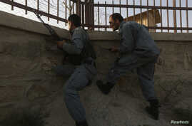 Afghan policemen take their positions at the site of an attack in Kabul, July 17, 2014.