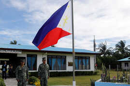 Filipino soldiers stand at attention near a Philippine flag at Thitu island in disputed South China Sea, April 21, 2017.