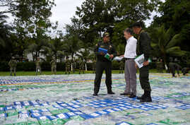 Colombia's President Juan Manuel Santos looks at the seizure of more than 12 tons of cocaine in Apartado, Colombia, Nov. 8, 2017.