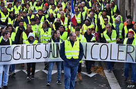 "Yellow Vests (Gilets jaunes) march behind a banner reading ""Yellow vests are angry"" as they protest high fuel prices in Rochefort, southwestern France, Nov. 24, 2018, part of a movement which has spread into a widespread protest against stagnant spen"