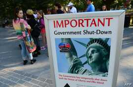 Tourists walk around sign announcing US government shutdown, Oct. 1, 2013.
