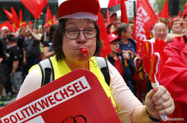 "A supporter of the Confederation of German Trade Unions (DGB) blows a whistle as she takes part in a union rally for ""political change"" in Frankfurt, Sept. 7, 2013."
