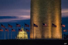 Flags around the Washington Monument fly in the breeze at daybreak, Dec. 31, 2015. Tourism experts fear President Trump's travel ban may hurt tourism across the United States.
