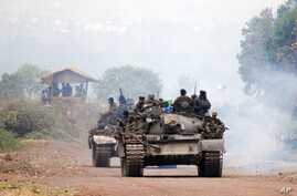 Congolese government troops ride armored vehicles toward the front line, near the eastern city of Goma, Democratic Republic of Congo, July 17, 2013.