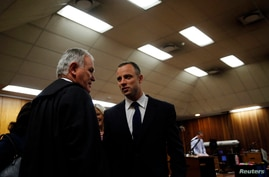 Olympic and Paralympic track star Oscar Pistorius confers with his defense lawyer, Barry Roux, in the North Gauteng High Court in Pretoria, May 6, 2014.