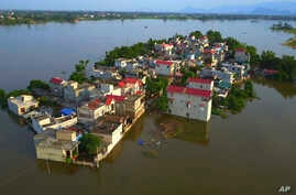 In this photo taken on July 22, 2018, a village is submerged in flood water in the suburb of Hanoi, Vietnam. (Vietnam News Agency via AP)