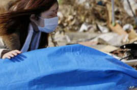 Tayo Kitamura kneels in the street to caress and talk to the wrapped body of her mother Kuniko Kitamura, after Japanese firemen discovered the dead woman inside the ruins of her home in Onagawa,  March 19, 2011