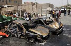 People inspect the aftermath of a car bomb attack in Sadr City, Baghdad, Iraq, July 23, 2012.