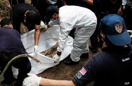 Malaysian police forensic team members excavate an unmarked grave in Wang Burma at the Malaysia-Thailand border outside Wang Kelian, Malaysia, May 26, 2015.