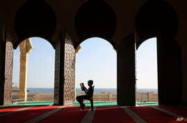 A Palestinian youth reads verses of the Quran, Islam's holy book, during the holy Islamic month of Ramadan at the beach side Mosque in Gaza City, June 9, 2016.