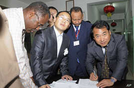 Chinese Embassy representatives sign handover papers to receive the body of a Chinese worker killed during a kidnapping, from a Sudanese Red Crescent representative (L) and a Sudanese Foreign Ministry official at the Chinese-run Hawasha hospital, in