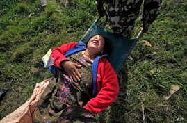 A woman, injured in Saturday's earthquake, is carried on a stretcher after being evacuated from Melamchi in an Indian Air Force helicopter, at the airport in Kathmandu, Nepal, May 1, 2015.