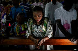 Congolese worshipers listen to Msg. Fridolin Ambongo, the the newly appointed Archibishop of Kinshasa, deliver the homily during an early midnight mass at the Notre Dame du Congo Cathedral in Kinshasa, Congo, Monday Dec. 24, 2018.