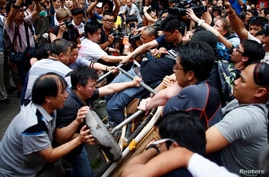 Anti-Occupy Central protesters (L) try to remove a barricade from pro-democracy protesters on a main street in Hong Kong's Mongkok shopping district, Oct. 4, 2014.